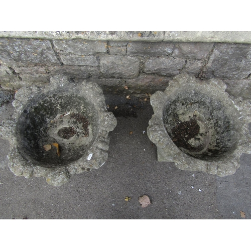 2004 - A pair of weathered composition stone garden urns with cabbage leaf bowls and square platform bases,...