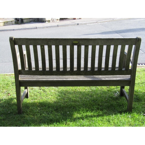 2021 - A weathered contemporary teak two seat garden bench with slatted seat and slightly curved slatted ba...