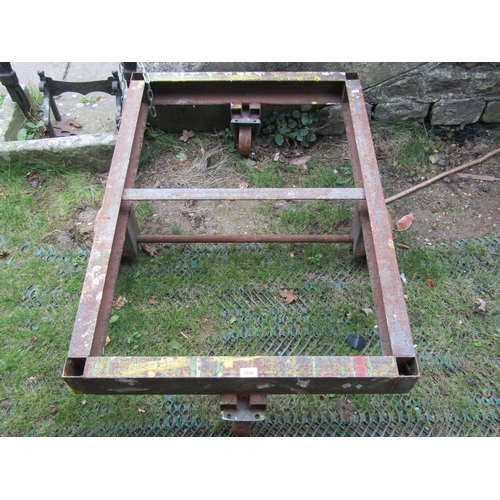 2049 - A low industrial fabricated steel framed platform trolley frame with four cast iron wheels, 112 cm x...