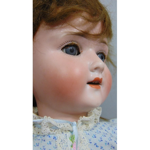 12 - A Schoenau & Hoffmeister bisque socket head doll, with weighted sleeping blue eyes and open mouth wi...