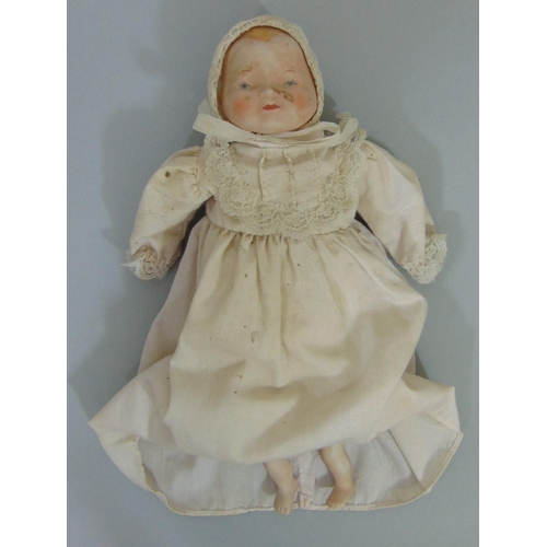 28 - Small baby doll with rocking crib: doll has bisque shoulder head with cloth body and bisque lower ar...