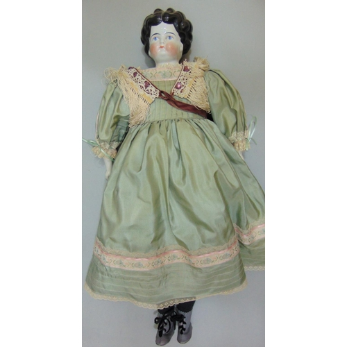 29 - Early glazed china shoulder-head doll, German circa 1890, with finely painted blue eyes, red line to...