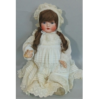 C1919 Bisque head baby doll by Bahr & Pröschild with composition body, bent limbs, closing blue eyes, open mouth with teeth and long hair in ringlets. Wearing period baby gown with velvet bonnet. Height 60cm. Impressed mark 'B & P' in a heart