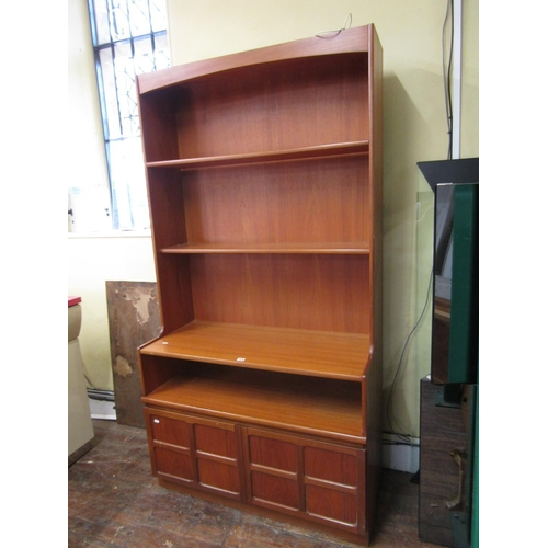 734 - A Nathan teak bookcase, the raised back over two panelled cupboard doors, 94cm high x 102cm wide...