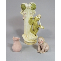 Early 20th century Royal Vienna Wahliss vase in the Royal Dux manner with applied figure of an Art Nouveau style female character, moulded and painted marks to base, 42 cm tall approx, together with a late 19th century continental bisque piano baby in the form of a seated child and also together with a pink ground relief moulded jug (3) all AF