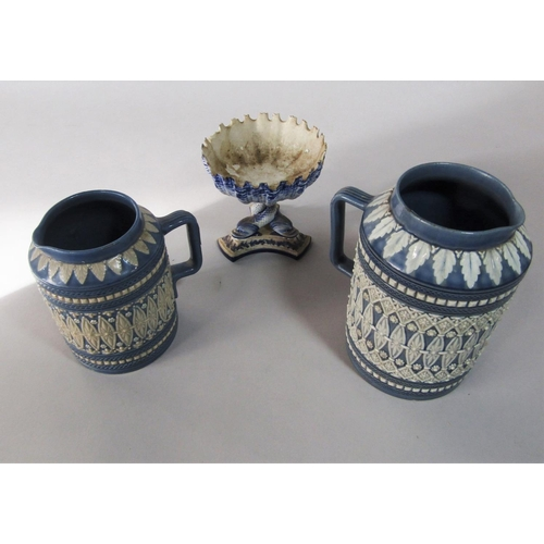 1027 - Two Doulton Lambeth graduated blue ground jugs with moulded lozenge and flower head detail in white ...