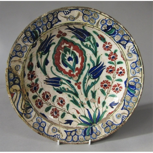 1030 - A early Persian dish with polychrome painted stylised tulip decoration, 29cm diameter (af)...