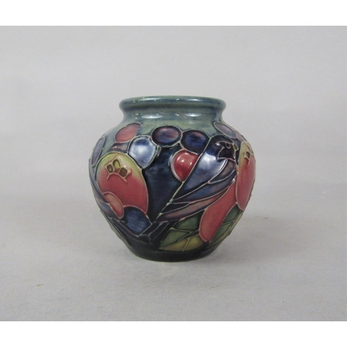 1050 - A Moorcroft low vase in the Finch and Fruit pattern with impressed marks to base, 7.5cm tall approx...