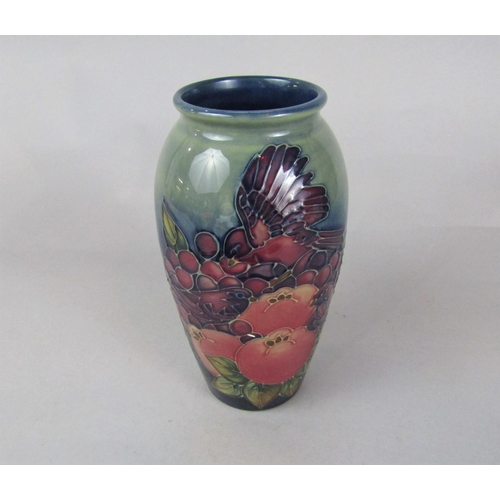1053 - A Moorcroft vase in the Finch and Fruit pattern with impressed marks to base and faint initials WM a...