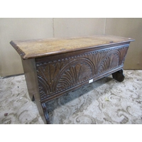 A small antique oak six plank coffer with hinged lid and carved front elevation, 90 cm wide x 36 cm deep x 42 cm in height