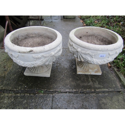 2014 - A pair of composition stone garden urns, of squat circular form with raised relief tied ribbon and s...