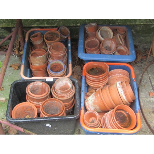 2024 - A quantity of small terracotta flower pots housed within four moulded plastic containers (AF)...