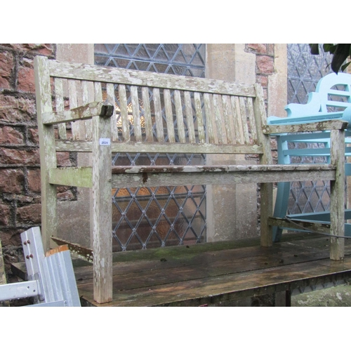 2029 - A weathered teak two seat garden bench with slatted seat and back, 128 cm long...