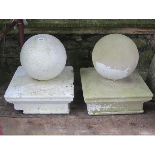 2030 - A pair of composition stone pier caps with sphere finials, the caps 43 cm square x 50 cm in height i...