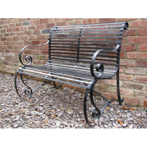 2042 - A sprung steel two seat garden bench with strap work seat and combined back, 108 cm wide...