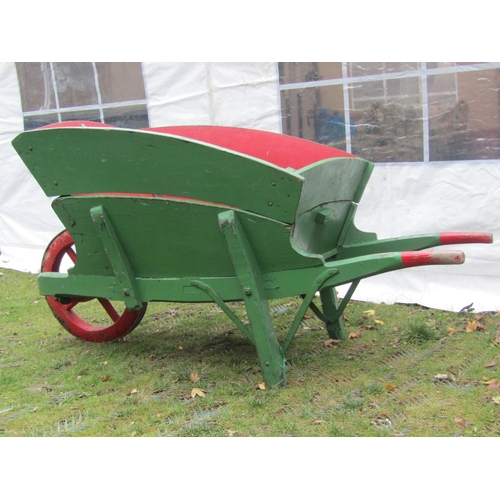 2052 - An antique traditional green and red painted wooden wheelbarrow, with chamfered detail, removable bo...