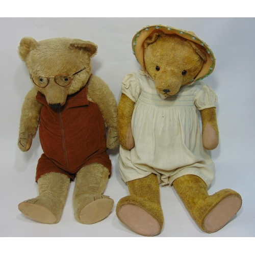 2 old teddy bears, both with  slightly humped back,    flat reinforced feet, glass eyes and stitched mouth; one bear is wearing spectacles and has stitched claws and the other is wearing a bonnet and baby dress, and is stuffed with wood wool. Both 67cm tall (2)