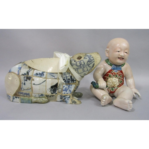1050 - A late 19th century oriental model of a seated baby holding a bird, with open mouth and painted pina...