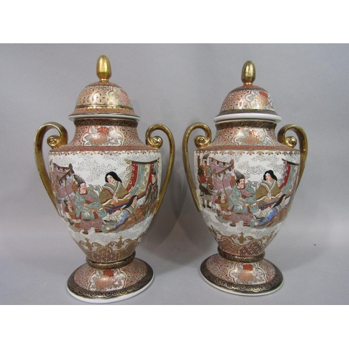 1052 - A pair of two handled oriental vases in the Satsuma manner with painted and gilded male and female c...
