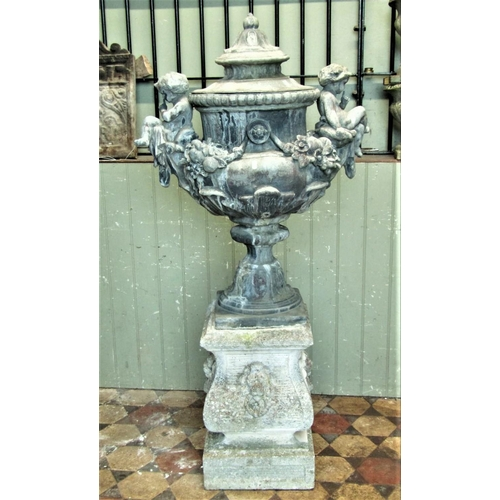 2097 - A weathered lead trophy shaped garden urn with removable lid, fruiting swags, seated cross legged ch...