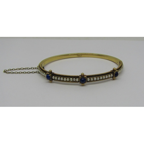 1338 - 18ct aesthetic movement hinged bangle set with lapis lazuli and seed pearls, 13.8g, contained in a J...