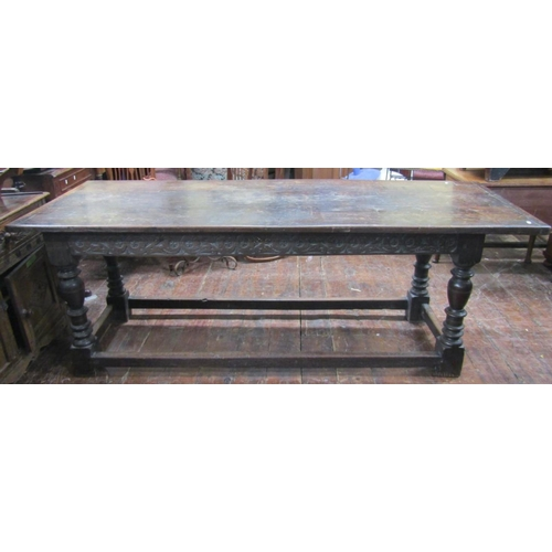 An antique oak refectory table, the plank top with cleated ends over a carved frieze (to all sides), raised on four turned supports united by outer rails, 215 cm in length x 78 cm wide x 80 cm in height
