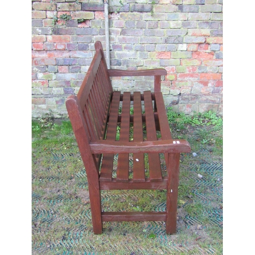 2013 - A good quality stained hardwood three seat garden bench with slatted seat and back, labelled manufac...