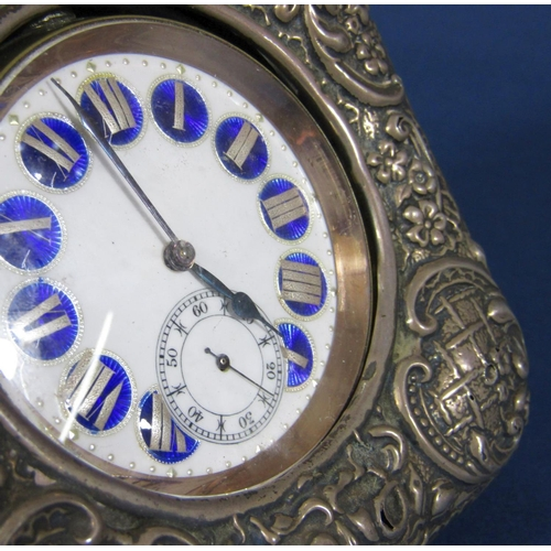 61 - A Goliath watch holder with embossed silver front and easel back supporting a silver plated watch, t...