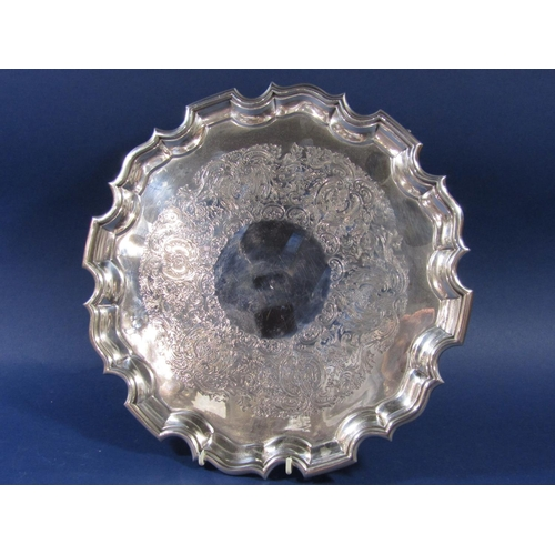 43 - Georgian style early 20th century silver salver, with pie crust rim and engraved foliate decoration,...