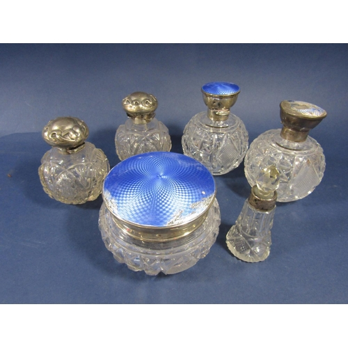 47 - A collection of silver topped dressing bottles to include three guilloche enamel examples (af) and t...