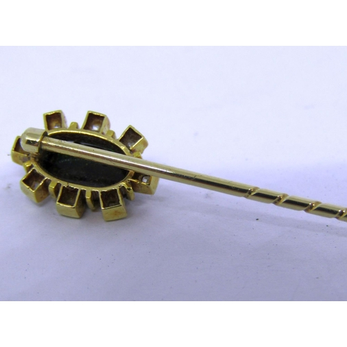 273 - Yellow metal stick pin set with an oval cabochon dark stone, possibly opal or ammolite, within diamo...