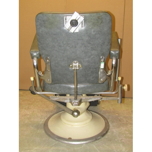 2022 - A vintage swivel and adjustable opticians chair with faux leather upholstered seat, back and arms, t...
