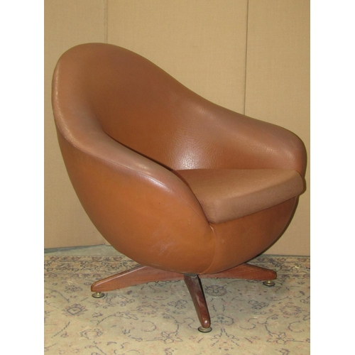 2027 - Two similar mid-20th century swivel egg type chairs with shaped outline, raised on sprung and crosse...