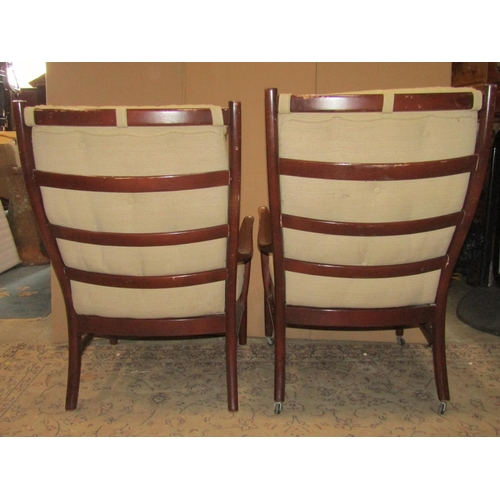 2028 - A pair of vintage mid-20th century Parker Knoll open armchairs, with moulded frames, sprung seats an...