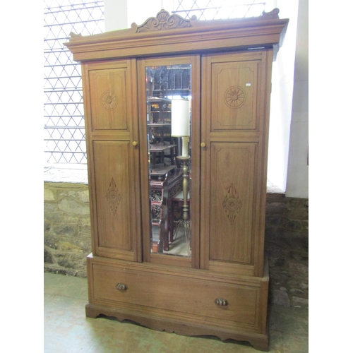 2052 - An Edwardian stripped walnut sectional wardrobe enclosed by three three-quarter length panelled door...