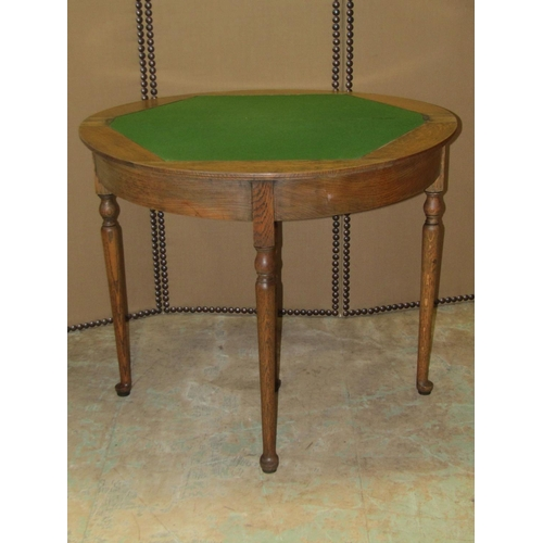 2054 - An oak demi-lune foldover top card table with moulded outline, raised on four simple turned tapered ...