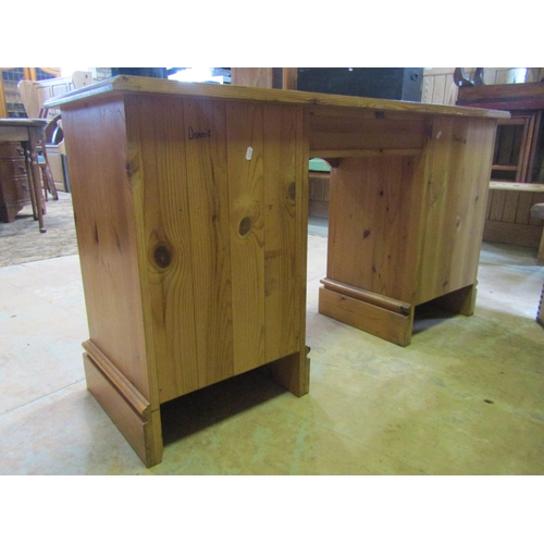 2056 - A contemporary pine kneehole dressing table/desk fitted with an arrangement of seven drawers with sw...
