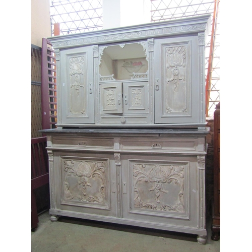 2045 - An antique two sectional buffet, enclosed by an arrangement of cupboards and doors with carved detai...