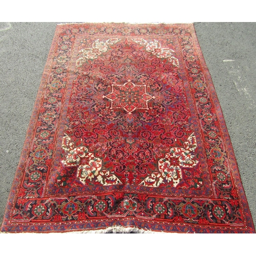 A good quality full pile Hamadan village carpet with scrolled floral and medallion decoration with central ivory panel upon a red ground, 320 x 230 cm