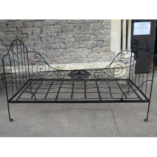 2001A - A antique ironwork folding single bedstead with arched head and footboard, decorative scroll and pie...