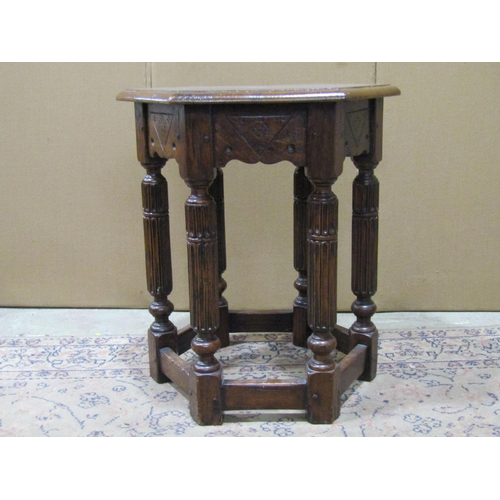 2046 - A good quality Old English style oak occasional table of hexagonal form raised on six fluted baluste...