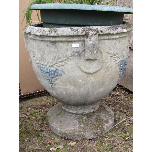 25 - A reclaimed garden urn with repeating fruiting vine detail, together with a further pot containing a...