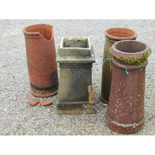 29 - Three terracotta chimney pots and a further buff coloured clay chimney pot, one (AF), 65 cm in heigh...