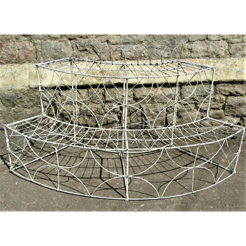 A Victorian ironwork demi-lune two tier plantstand with repeating decorative finish, 125 cm in length x 65 cm in height