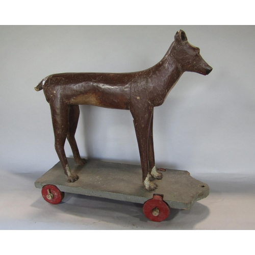 1681 - Good quality 19th century folk art carving of a standing hound upon a plinth base with wheels, paint...