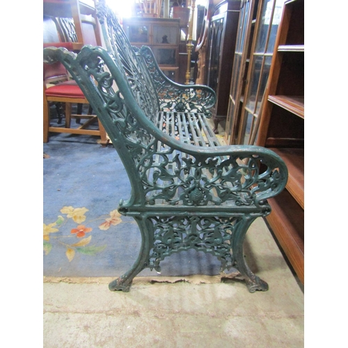 2223 - A pair of good quality heavy cast iron peacock pattern garden benches with decorative pierced detail...