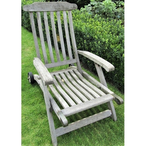 10 - A weathered teak garden reclining chair, mounted on a single axle (lacks foot rest)