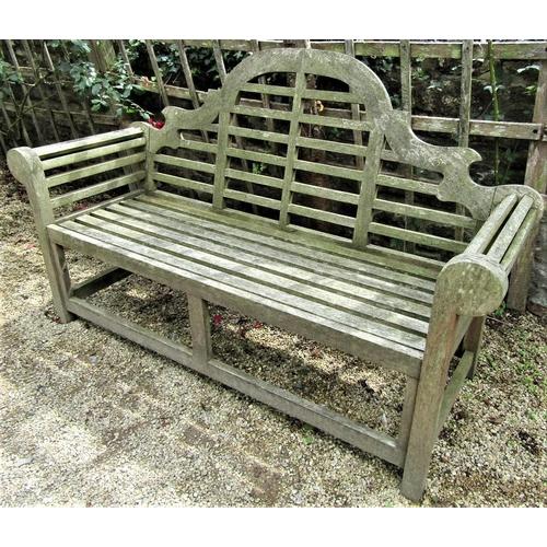 17 - A weathered teak wood garden seat in the Lutyens manner, 165cm wide
