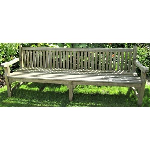 27 - A weathered teak wood garden bench, 240cm wide