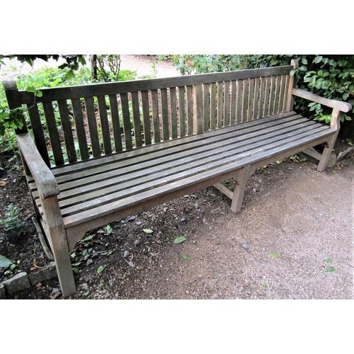 46 - A weathered teak wood garden bench, 240cm wide